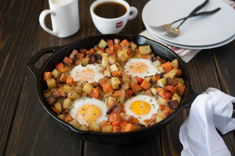 Potatoes are browned in a pan with 4 sunny side up eggs