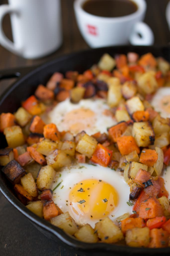Russet and sweet potatoes are browned in a cast iron skillet with sunny side up eggs