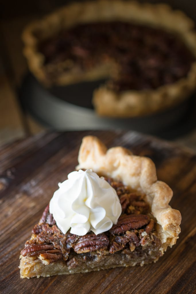 A slice of bourbon pecan pie with a dollop of cream on the top
