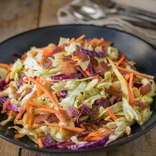 A closeup showing the red cabbage, green cabbage, orange carrot and crispy bacon