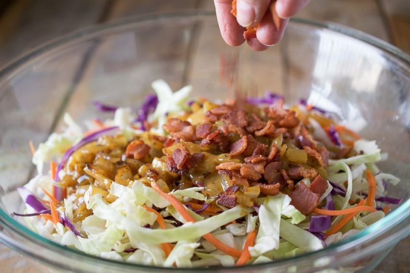 Crispy bacon being sprinkled onto the cabbage and vinaigrette