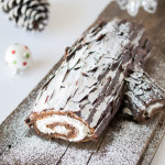 The Yule log on a wood plank dusted with powdered sugar to look like snow with a pine cone