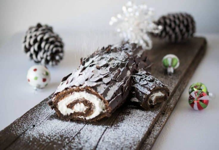 A Yule log on a plank of wood being dusted with powdered to sugar