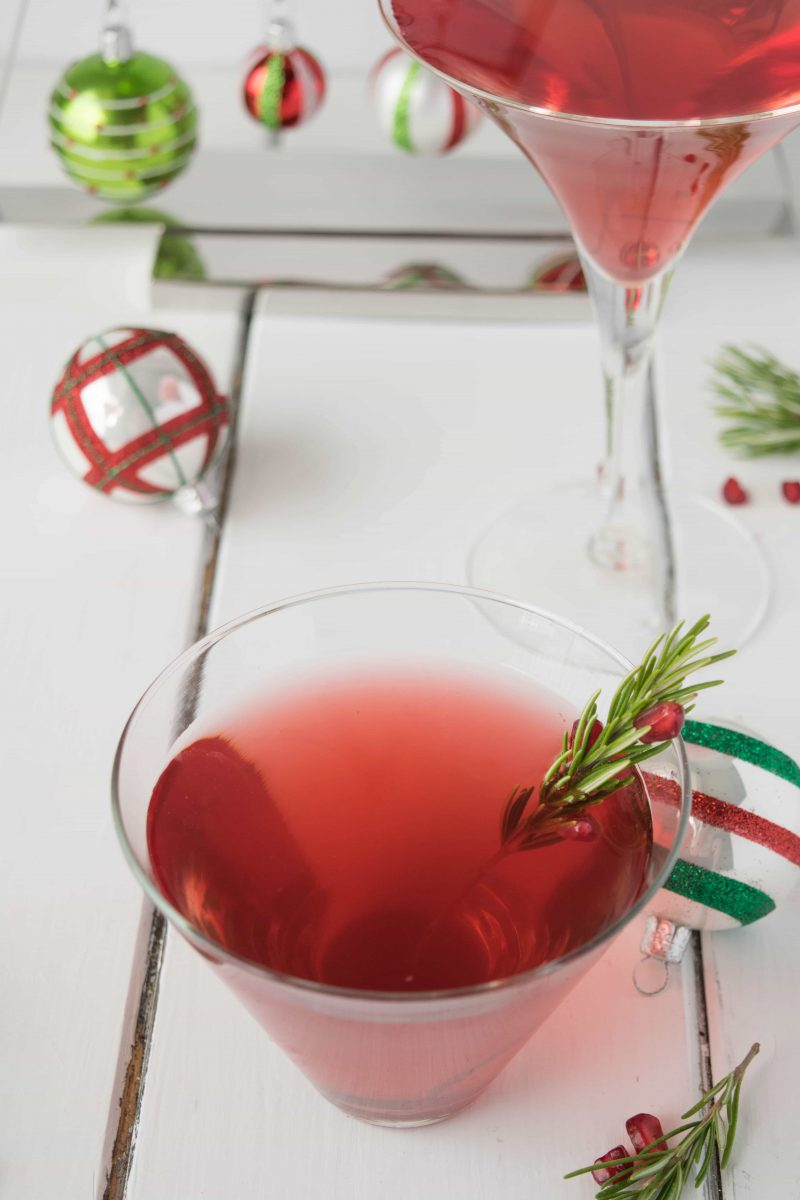 Christmas Cosmopolitan in a glass garnished with fresh rosemary