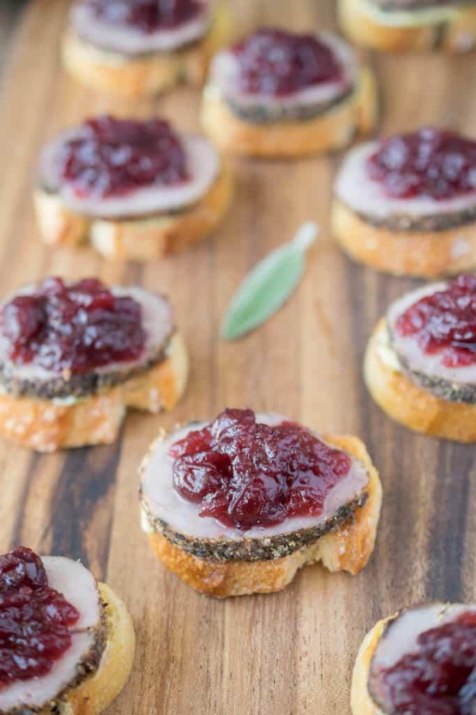 Pork and cranberry crostini. Tender roast pork tenderloin slices with sweet cranberry sauce, sage mustard on crispy baguette slices.