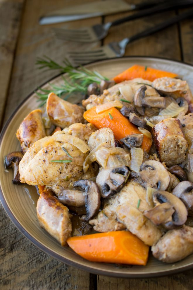 A plate of chicken and vegetables with fresh rosemary
