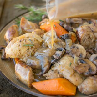 Pouring gravy over chicken and vegetables