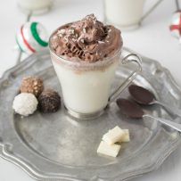 White hot chocolate with dark chocolate whipped cream on a pewter plate with chocolate dipped spoons and chocolate treats