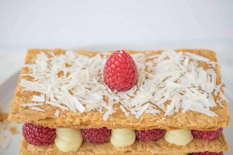 A closeup of the top showing shaved white chocolate and a raspberry