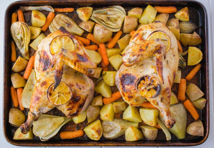 Two halves of a chicken and vegetables on a sheet pan