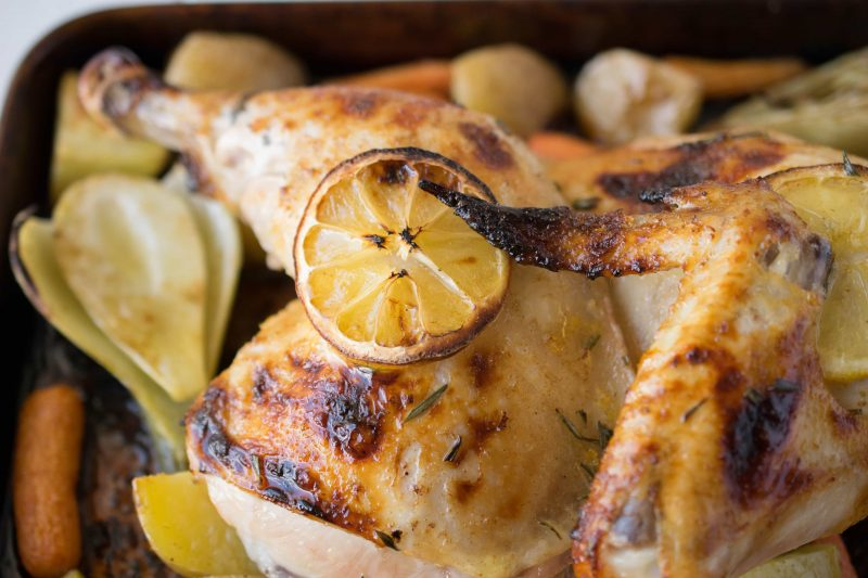 A closeup of half a roasted chicken with a slice of lemon