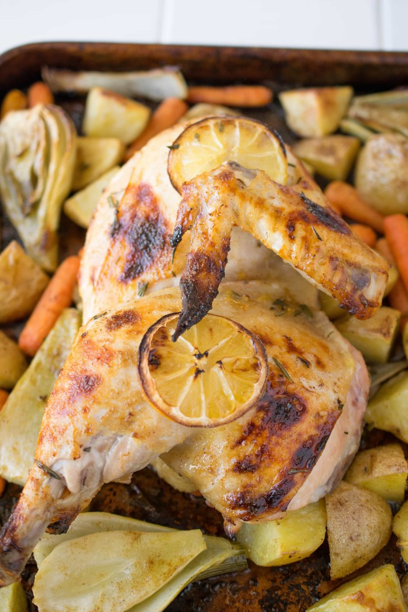Half of a roasted chicken on a baking sheet of vegetables