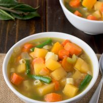 2 white bowls filled with vegetable soup with colors of yellow, orange and green