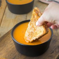 Dipping a grilled cheese sandwich in a bowl of 30 minute tomato basil soup
