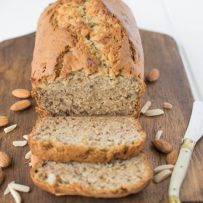 Almond banana bread sliced on a board with a knife and almonds
