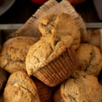 A wooden box with burlap draped over filled with apple pie pecan muffins