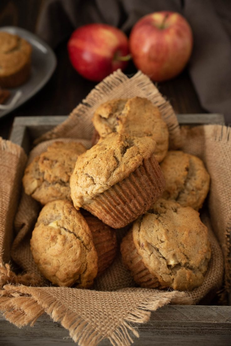 A wooden box full of muffins with red apples in the background