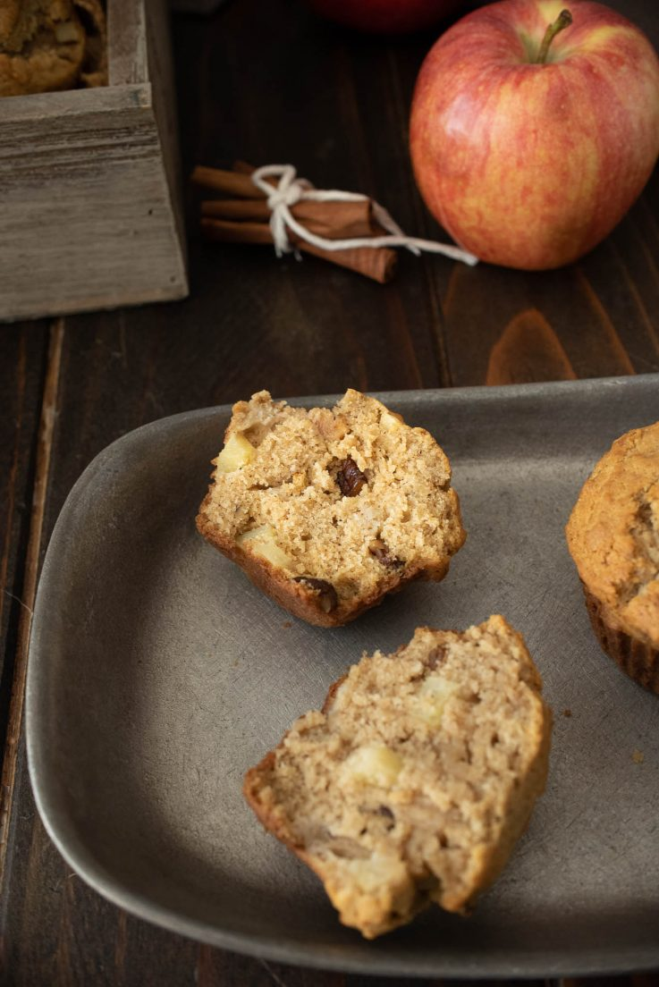 A muffin cut in half on a grey plate showing fresh apple and pecan inside