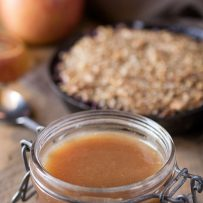 A jar of caramel sauce with a crumble dessert in the background