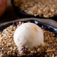 Apple and blackberry crumble in a mini cast iron skillet showing the filling of fresh blackberries and apple