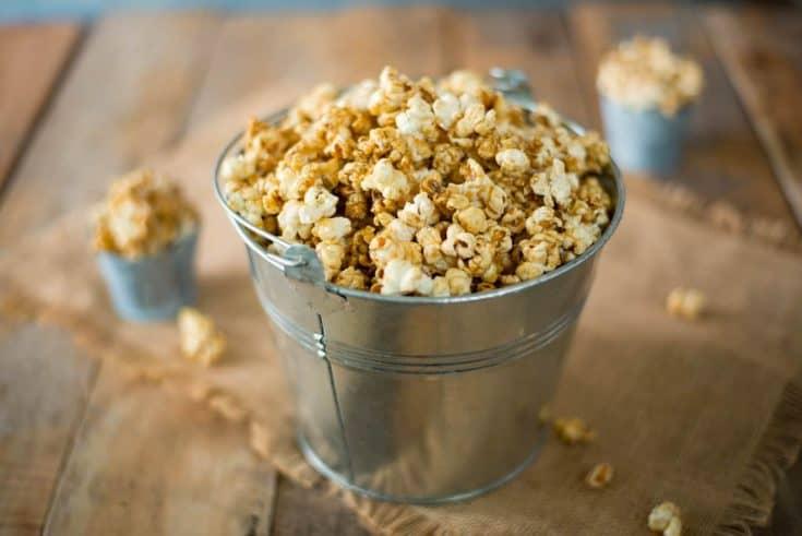 A silver bucket of of apple cider caramel popcorn