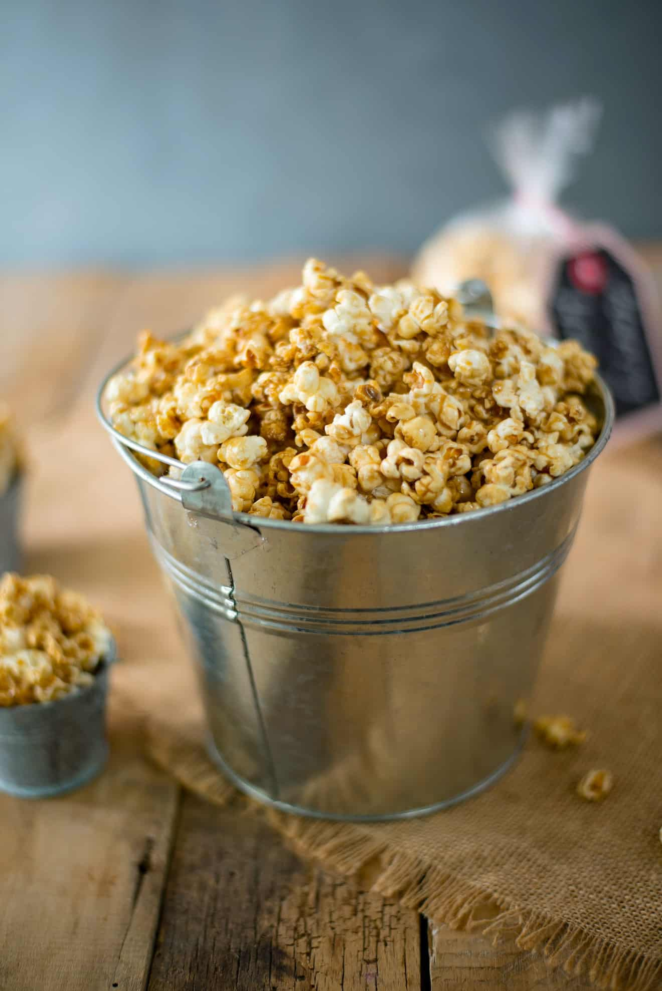 A silver bucket filled with Apple Cider Caramel Popcorn