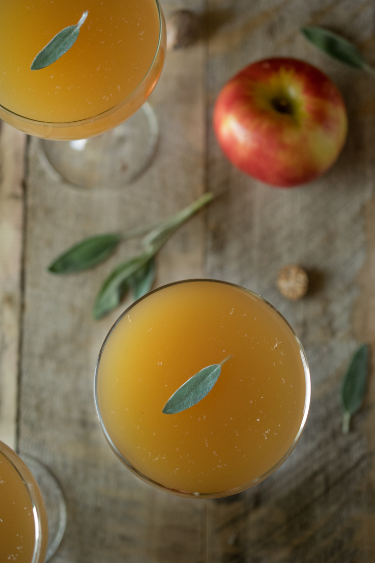The drink from above surrounded by sage leaves and a red apple