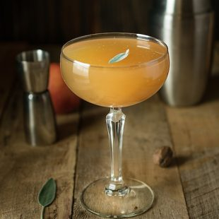 A lovely side image of the drink on a board with a cocktail shaker