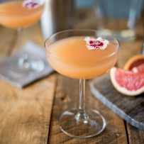 A coupe champagne glass of April Showers cocktail with a flower and grapefruit wedges
