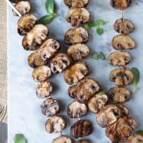 4 skewers of mushrooms on a marble board