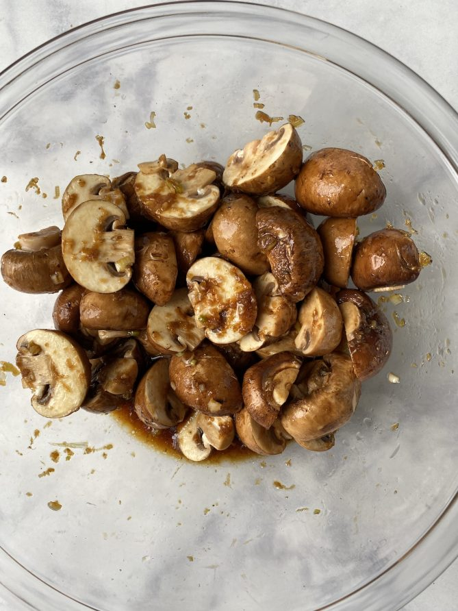 A bowl of mushroom halves marinating in a sauce in a glass bowl