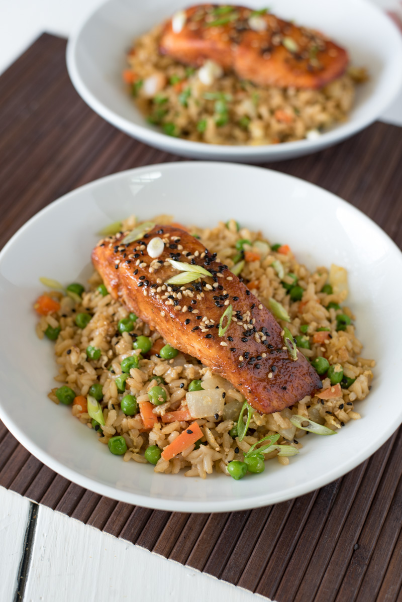 Vegetable fried rice with a filet of salmon on top all in a white bowl