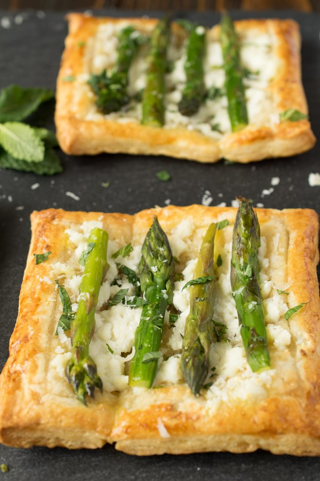 A closeup showing asparagus sprigs on top of a puff pastry tartlet