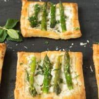2 asparagus ricotta mint tartlets on a slate serving board