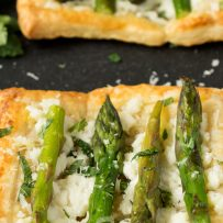 4 asparagus sprigs on top of a ricotta, mint and puff pastry tart