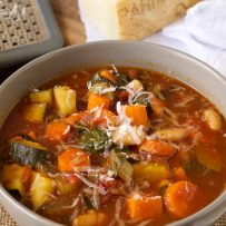 Orange and green vegetables in minestrone soup with grated Parmesan cheese