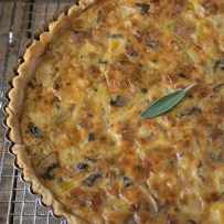 A whole quiche just out of the oven on a cooling rack