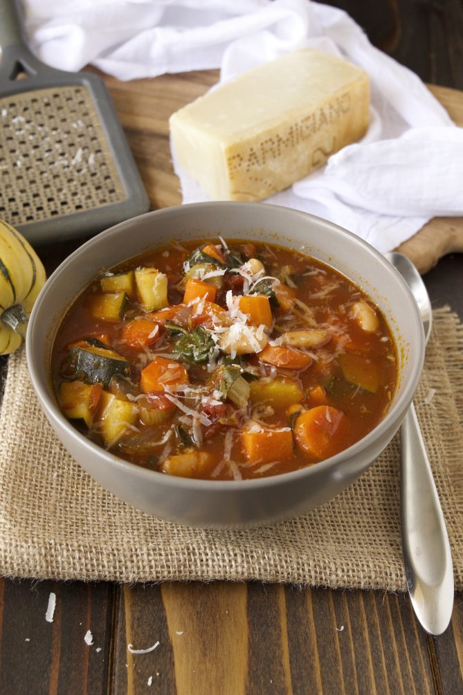 Autumn minestrone in a grey bowl topped with grated Parmesan cheese