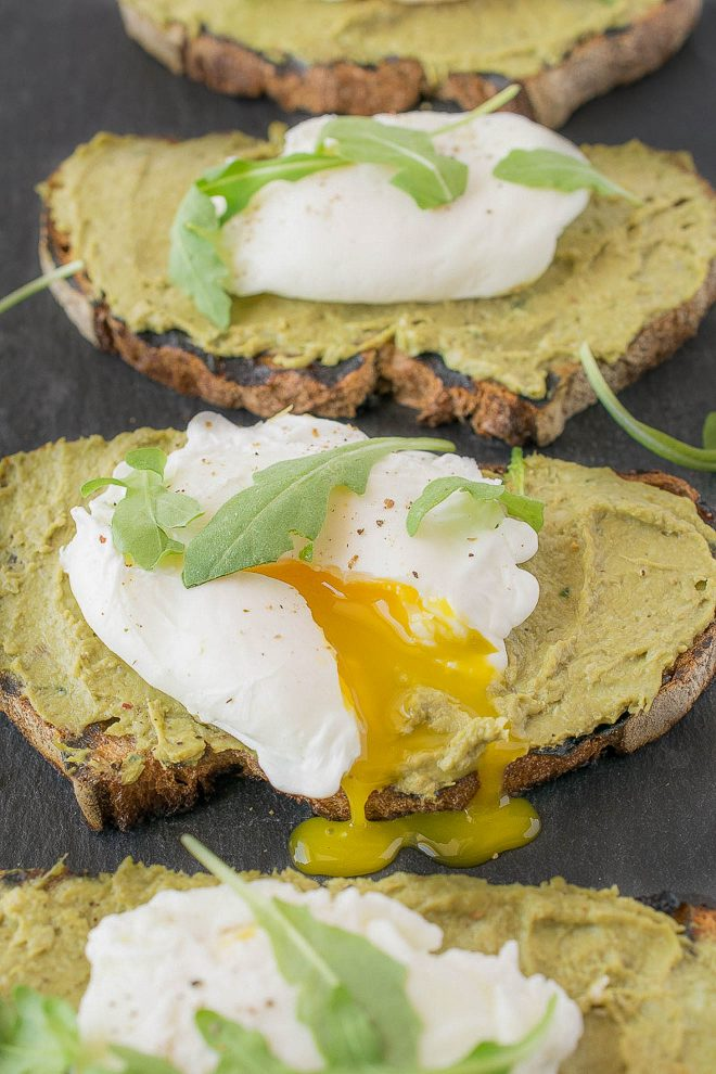 A perfectly poached egg with the yolk running out onto avocado artichoke toast