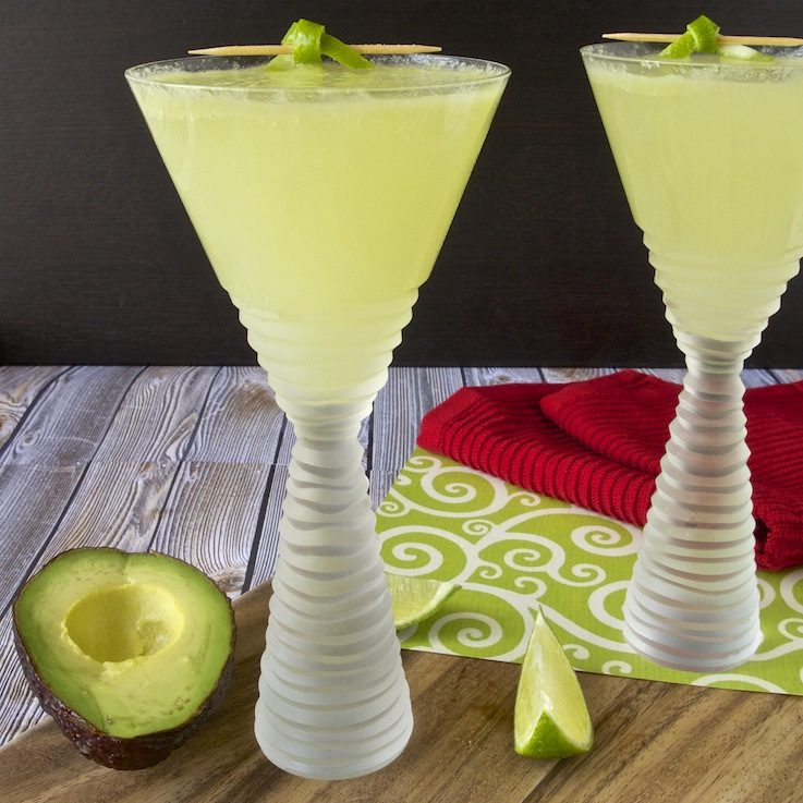 2 avocado martinis on a board with half an avocado and lime wedges