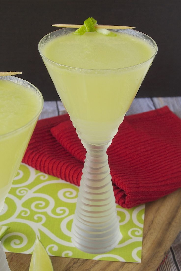 An avocado martini in a pretty frosted glass garnished with lime peel