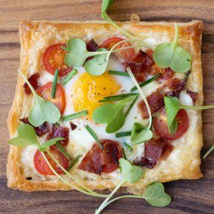 A square of puff pastry topped with cheese, tomatoes, bacon, egg, chives and greens