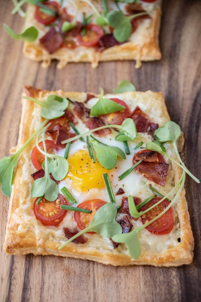 A breakfast tart up close showing the yellow egg and sweet cherry tomatoes
