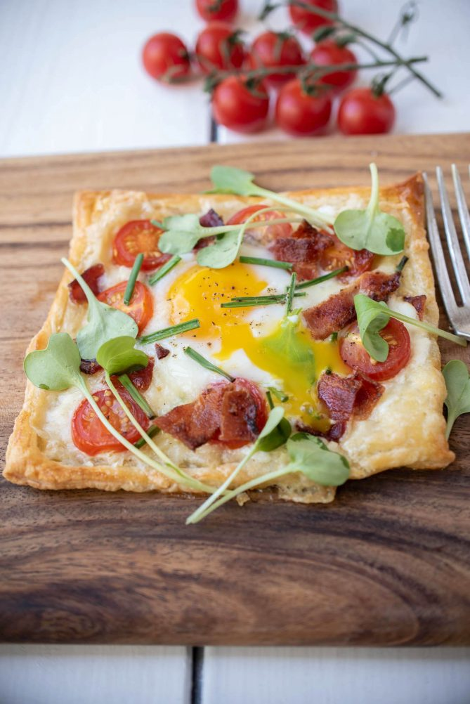 Bright yellow egg yolk running over the puff pastry and crispy bacon