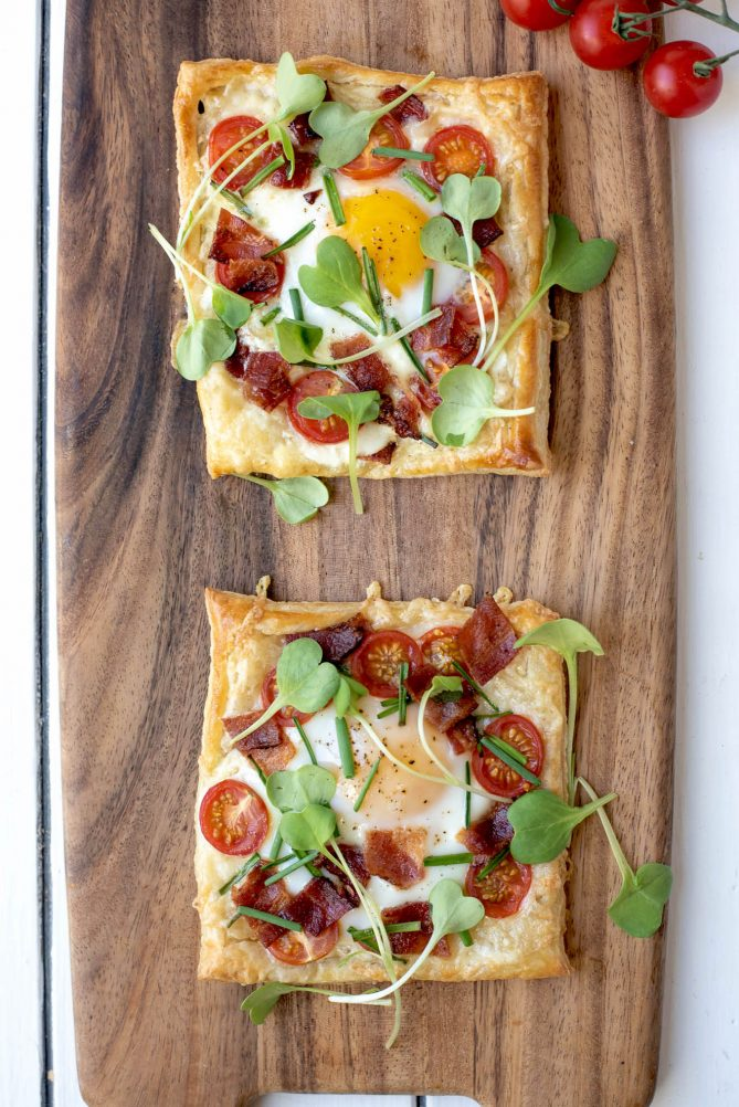 2 bacon egg and tomato puff pastry tarts viewed from overhead