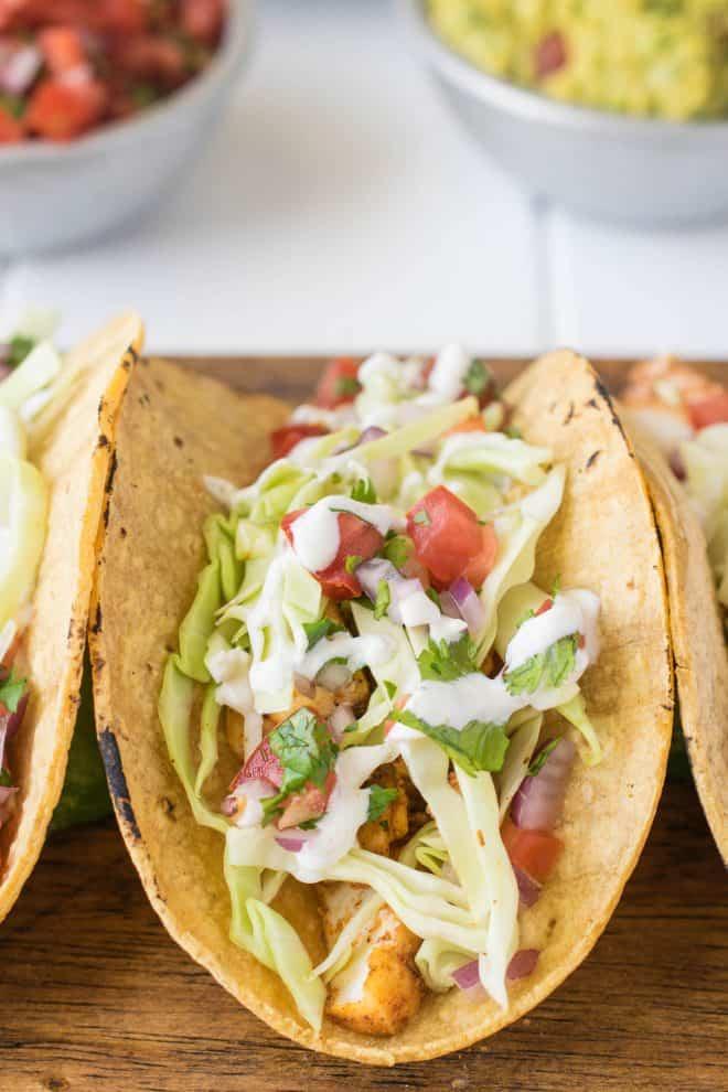 A healthy fish taco topped with pico de gallo, cabbage and crema