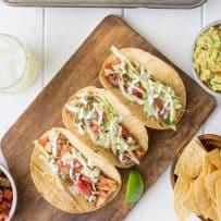 A feast of fish tacos, tortilla chips, salsa, guacamole and a lemon lime margarita
