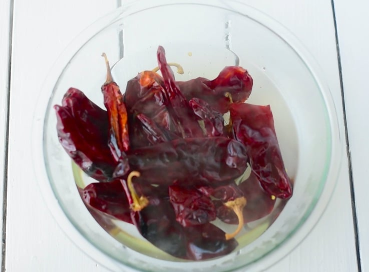 Guajillo peppers are softened in boiling water