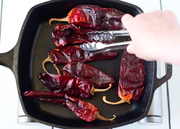 Dried guajillo peppers toasting in a cast iron skillet