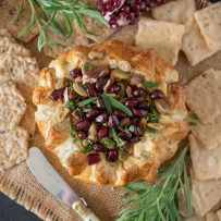 From overhead showing the pretty pomegranate seeds and rosemary on top of the baked brie